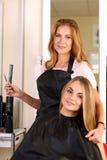 Schöner blonder weiblicher Friseur, der herein Scheren und Kamm hält Lizenzfreie Stockfotografie