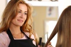 Schöner blonder weiblicher Friseur, der Scheren in den Händen hält Stockbilder