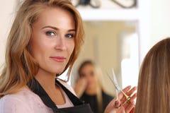 Schöner blonder weiblicher Friseur, der Scheren hält Stockbild
