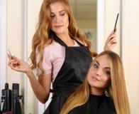Schöner blonder weiblicher Friseur, der Scheren und Kamm hält Lizenzfreies Stockfoto