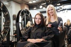 Schöner blonder weiblicher Friseur, der Scheren und Kamm hält Stockfotografie