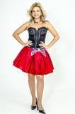 Schöner Blondinekünstler in chermnm Korsett mit Pailletten und roter Rock mit Gurt beugen lizenzfreie stockfotografie