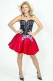 Schöner Blondinekünstler in chermnm Korsett mit Pailletten und roter Rock mit Gurt beugen lizenzfreies stockbild