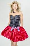 Schöner Blondinekünstler in chermnm Korsett mit Pailletten und roter Rock mit Gurt beugen lizenzfreie stockfotos
