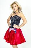 Schöner Blondinekünstler in chermnm Korsett mit Pailletten und roter Rock mit Gurt beugen Lizenzfreies Stockfoto