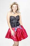 Schöner Blondinekünstler in chermnm Korsett mit Pailletten und roter Rock mit Gurt beugen stockfotos
