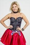 Schöner Blondinekünstler in chermnm Korsett mit Pailletten und roter Rock mit Gurt beugen stockfotografie