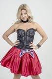 Schöner Blondinekünstler in chermnm Korsett mit Pailletten und roter Rock mit Gurt beugen stockbilder