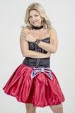 Schöner Blondinekünstler in chermnm Korsett mit Pailletten und roter Rock mit Gurt beugen stockbild