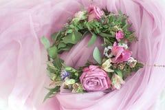 Schöner Blumenkranz mit dem bunten Blühen blüht auf rosa Schleier Stockfotografie