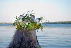 Schöner Blumenstrauß des Kranzes der wilden Blumen auf dem Mädchenkopf nahe dem Wasserfluß Lizenzfreie Stockbilder