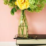 Schöner Blumenstrauß von Blumen im Glasvase auf einem Stapel Büchern vor blassem - rosa Pastellhintergrund Lizenzfreie Stockfotos