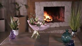 Schöner Blumenstrauß von Pastellfarbblumen in den rosa dekorativen Papierständen auf den Stämmen auf einer grauen Tabelle nach de stock footage