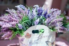Schöner Blumenstrauß von purpurroten Blumen in der Tasche mit der Aufschrift Liebe Lizenzfreie Stockfotos
