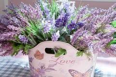Schöner Blumenstrauß von purpurroten Blumen in der Tasche mit der Aufschrift Liebe Lizenzfreie Stockbilder