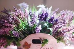 Schöner Blumenstrauß von purpurroten Blumen in der Tasche mit der Aufschrift Liebe Lizenzfreies Stockfoto