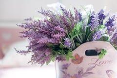 Schöner Blumenstrauß von purpurroten Blumen in der Tasche mit der Aufschrift Liebe Lizenzfreies Stockbild