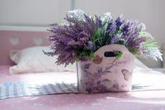 Schöner Blumenstrauß von purpurroten Blumen in der Tasche mit der Aufschrift Liebe Stockbilder