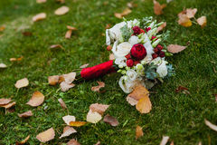Schöner Blumenstrauß von roten und weißen Rosen auf grünem Gras mit gelben Blättern Lizenzfreies Stockbild
