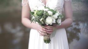 Schöner Blumenstrauß von verschiedenen Farben in den Händen der Braut in einem weißen Kleid Braut im weißen Kleid mit Blumenstrau stock footage