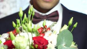 Schöner Blumenstrauß von weißen Rosen und von roten Blumen in den Händen des Mannes in der Jacke in der roten Fliege und im weiße stock video