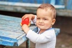 Schöner braunäugiger kleiner Junge, der mit einem roten Plastikspielzeug c spielt stockbilder
