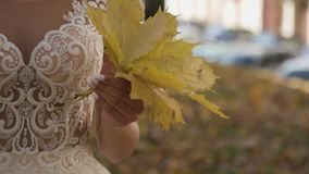 Schöner Brautblumenstrauß in den Händen der jungen Braut kleidete im weißen Hochzeitskleid an Schließen Sie oben vom großen Bünde stock footage