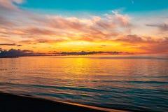 Schöner brennender Sonnenunterganghimmel auf dem Strand stockbild