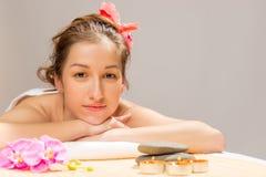 Schöner Brunette auf einem Tuch in einem Badekurort Stockbild