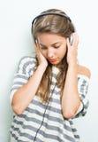 Schöner Brunette in den Kopfhörern, Augen geschlossen. Lizenzfreie Stockfotografie