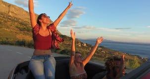 Schöner Brunette, der auf Haube des Kabrioletts beim Reiten mit ihren Freunden sitzt stock video footage