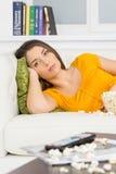 Schöner Brunette, der auf weißer Couch liegt Lizenzfreie Stockfotografie