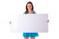Schöner Brunette, der leeren weißen Vorstand anhält Stockfoto