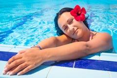 Schöner Brunette, der am Swimmingpool sich entspannt Stockfotografie