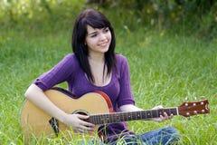 Schöner Brunette draußen mit einer Gitarre (1) Stockfotos