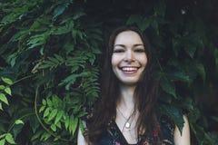 Schöner Brunette in einem grünen Laub, lächelnd stockfoto