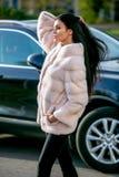 Schöner Brunette in einem hellfarbigen Mantel und schwarzen Hosen des Pelzes geht hinunter die Straße vor dem Auto an einem sonni stockfoto