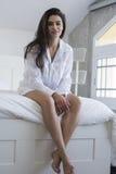 Schöner Brunette in einem weißen Hemd, das auf einem Bett aufwirft lizenzfreies stockbild