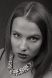 Schöner Brunette in einer stilvollen Form auf einem dunklen Hintergrund Stockfotografie