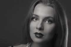 Schöner Brunette in einer stilvollen Form auf einem dunklen Hintergrund Stockfotos