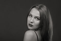 Schöner Brunette in einer stilvollen Form auf einem dunklen Hintergrund Lizenzfreies Stockfoto
