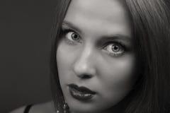 Schöner Brunette in einer stilvollen Form auf einem dunklen Hintergrund Stockfoto