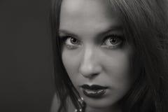Schöner Brunette in einer stilvollen Form auf einem dunklen Hintergrund Lizenzfreie Stockbilder