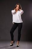 Schöner Brunette in einer stilvollen Form auf einem dunklen Hintergrund Lizenzfreie Stockfotos