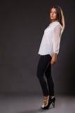 Schöner Brunette in einer stilvollen Form auf einem dunklen Hintergrund Lizenzfreie Stockfotografie