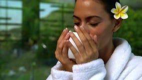 Schöner Brunette im Bademantel Kräutertee am Badekurort trinkend stock video