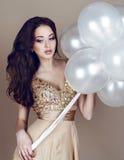 Schöner Brunette im luxuriösen beige Kleid, das ein Weiß hält, steigt im Ballon auf Stockbild
