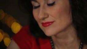 Schöner Brunette im roten Kleid, das mit a spielt stock video