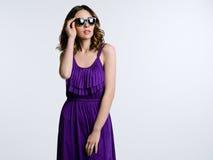 Schöner Brunette im violetten Kleid Lizenzfreie Stockfotos