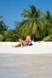 Schöner Brunette liegt auf einem weißen Strand Stockfoto